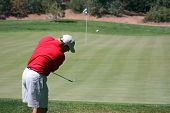 Man Chipping Ball Onto Green, Focus On Golfer