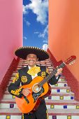 Charro Mariachi singer playing guitar in Mexico stairway