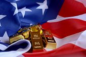 A Closeup Of An American Flag With A Stack Of Pure Gold Bullion Bars For Financial Concepts. poster