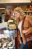Woman looking at chocolate and treats by shop window