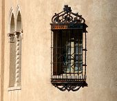 Ornate iron grated window in adobe wall