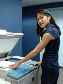 A young Asian girl working at a busy office copy machine.