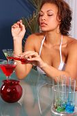 Sexy bikini clad bartender mixing her own special martini