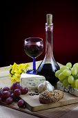 stock photo of jonquils  - Romantic dinner with cheese wine grapes and jonquils on rustic board