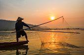 Fisherman On Boat River Sunset / Asia Fisherman Net Using On Wooden Boat Casting Net Sunset Or Sunri poster