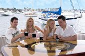 Two young couples share a cup of coffee on the aft deck of a private yacht after a long day at sea