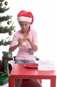 A young girl sitting by the Christmas Tree eating dipping the last of Santa's cookies in her glass of milk