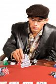 Hispanic man looking at his hole cards while playing Texas Hold um poker.