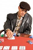 Hispanic man looking at his hole cards while playing Texas Hold um poker. Problem is he is wearing glasses that reflect his hand