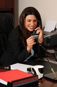 Happy business woman on her office phone and using a credit card to pay for a purchase