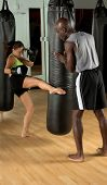 Beautiful but dangerous woman fighter working with her trainer kicking a heavy bag in an Mixed Martial Arts gym.