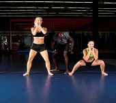 Young female MMA fighters doing power squats in the gym with their trainer.  Focus on on the right i