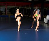 Young female MMA fighters working on high knee kicks with their personal trainer in the gym