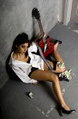 picture of crackhead  - Young woman in a white mans shirt and black lingerie with a guitar and a small pile of cash on the ground - JPG