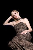 Beautiful young blond woman in an animal print evening gown sitting against a black hassock on a black background