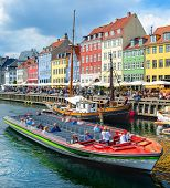 Tourists Sightseeing Cruising On Boat By Nyhavn Embankment With Bars And Restaurants In Buildings Of poster