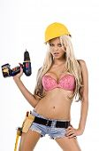 High fashion glamour model in Daisy duke shorts, tool belt, pink bra and yellow hard hat with a scre