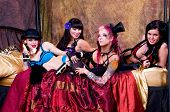 image of trouble-maker  - Rabble rousing group of burlesque dolls dancers gathered on the bed of their dressing room - JPG