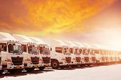 New Haulage Truck Fleet Is Parking Narrow At Yard With Sunset Warm Tone Beautiful Sky. poster