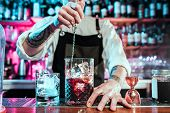 Expert Barman Is Making Cocktail At Night Club Or Bar. Glass Of Fiery Cocktail On The Bar Counter Ag poster