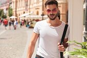 portrait of handsome young man holding shoulder bag and wearing sunglasses while sightseeing the cit poster