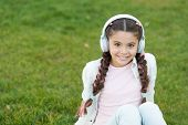 Kid Girl Enjoy Music While Sit On Green Grass Meadow. Pleasant Leisure Time. Child Headphones Listen poster