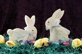 pic of peter cottontail  - Two wooden Easter Bunnies are displayed here with Easter grass chocolate Easter eggs yellow tulips - JPG