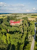 Aerial Photo Of Old Castle Turned Into School In Countryside Between Trees With Dramatic Clouds Over poster