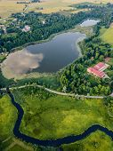 Aerial Photo Of Countryside Village Between Trees And With Big Blue Lake Besides It In Early Spring poster