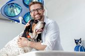 Portrait of smiling doctor with dog at veterinary clinic poster