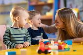 Nursery Children Building Blocks With A Teacher In Preschool Playroom poster