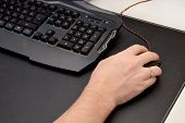 Guy Is Playing A Video Game. Close Up Of A Hand Lying On A Laptop Mouse And A Black Gaming Keyboard  poster