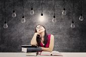 stock photo of indian  - Portrait of smart female college student with books and bright light bulb above her head as a symbol of bright ideas - JPG