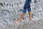Slender Woman's Legs In Water Cascade