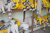 stock photo of firehose  - Yellow firehose are hanging on warehouse steel shelfs - JPG