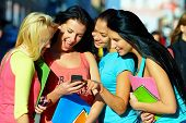 Group Of Female Students Chatting In Social Network On Mobile Phone