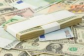 stock photo of ten thousand dollars  - ten thousand dollars on heap of dollars and euro - JPG