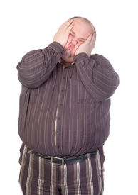 stock photo of bulging belly  - Obese man standing squashing his face with his hands with his buttons popping open over his huge belly isolated on white - JPG