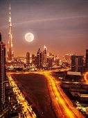 Dubai in moonlight, UAE, full moon, night scape in Dubai downtown, modern Arabian architecture, midd