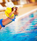 Little girl jumping into the pool, active lifestyle, sportive sweet child, water amusement, swimming
