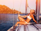 Sexy woman tanning on yacht, enjoying warm sunlight, seductive model wearing white stylish swimwear and posing on deck of sailboat in sunset light, summer holidays