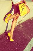 woman  tan legs in yellow high heel shoes and purse on street summer day
