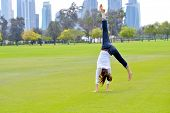 pretty healthy young woman jump and exercise fitness on grass in green park with city in background