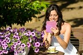 Woman Reading Ebook In Garden