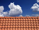 stock photo of red roof tile  - Roof tiles against blue sky with clouds - JPG