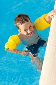 Smiling boy having a fun at swimming pool with water wings and snorkel