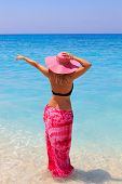 Summer vacation woman on the beach in beach straw hat and sarong looking at the ocean