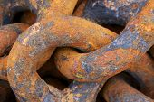 picture of oxidation  - Steel anchor chains caked with rust at an industrial port facility.