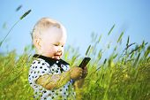 little boy in green grass call by phone
