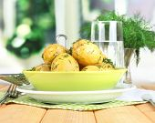 Boiled potatoes on platens on on napkins on wooden table on window background